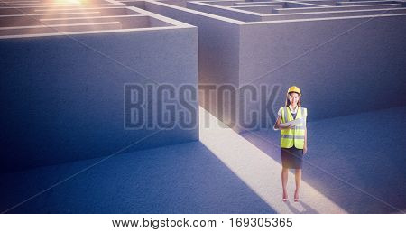 Architect woman with yellow helmet and plans against entrance to difficult maze puzzle