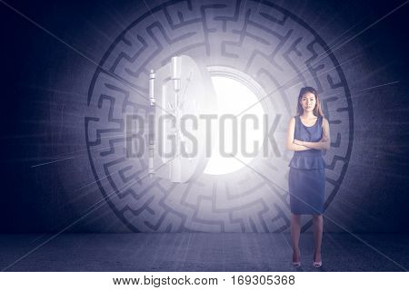 Businesswoman with crossed arms against open safe in middle of maze on black wall