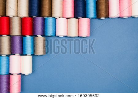 Top view of colorful thread spools over blue seamless background. Image taken from above.