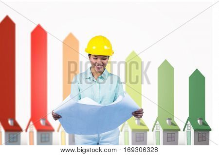 Architect reading a plan with yellow helmet against seven 3d houses representing energy efficiency