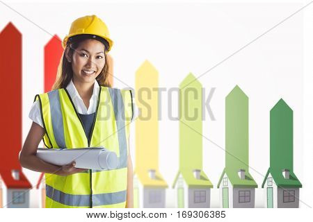 Architect woman with yellow helmet and plans against seven 3d houses representing energy efficiency