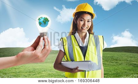 Architect woman with yellow helmet and plans against blue sky over green field