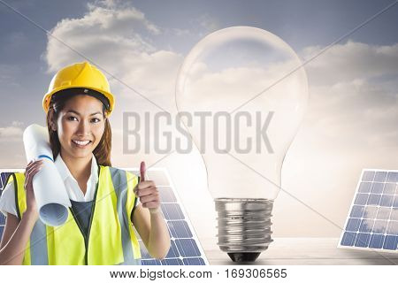 Architect woman with thumbs up against light bulb and solar panels on floorboards in the sky