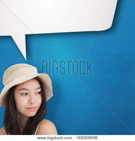 Woman with a straw hat looking away against blue background with vignette