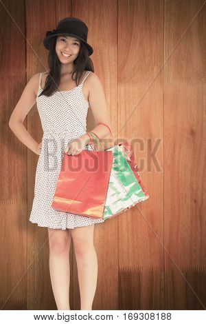 Pretty woman with shopping bags against wooden flooring