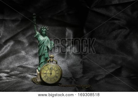Statue Of Liberty With Vintage Pocket Watch On Black Fabric Background. Still Life Photography