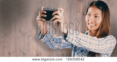 Smiling asian woman taking picture with camera against wooden planks