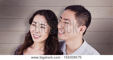 Cheerful couple looking away against bleached wooden planks background