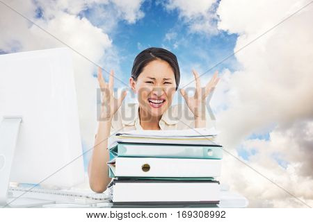 Blue sky with white clouds against angry businesswoman shouting with stack of folders at desk