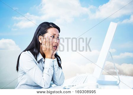 Exhausted businesswoman with hands on face against cloudy sky