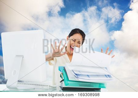 Businesswoman shouting with stack of folders at desk against blue sky with white clouds