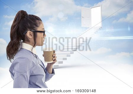 Businesswoman holding disposable cup and looking at wall with notes against steps leading to open door in the sky