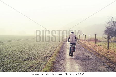 Old man on a bicycle, winter scene with dirt road, fields and fog. Tranquil scene.