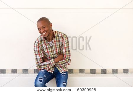 Happy Young African American Man Sitting With His Arms Crossed