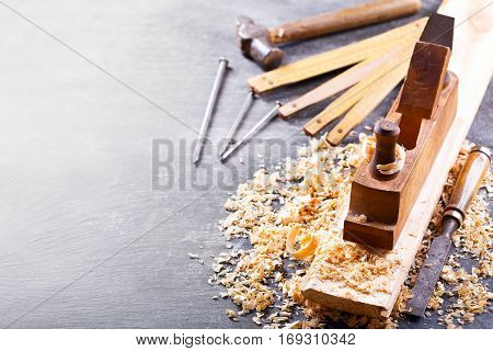 old tools: wooden planer hammer chisel in a carpentry workshop on dark background