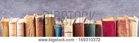 various old books on a shelf on dark background banner