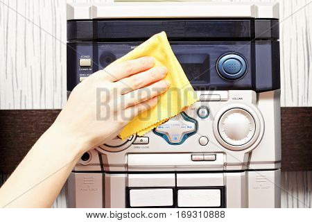 A woman holds a thorough cleaning cloth musical center.