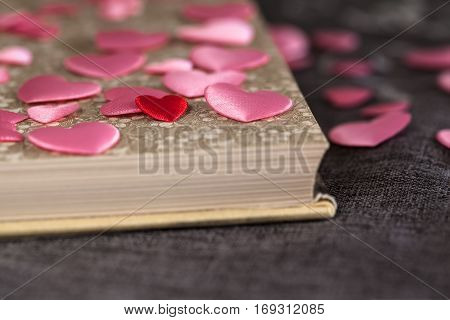 Detail of one very small red heart among many pink ones and open vintage book on brown textile surface (copy space)