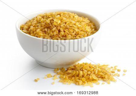Dry Bulgur Wheat In White Ceramic Bowl Isolated On White. Spilled Bulgur.