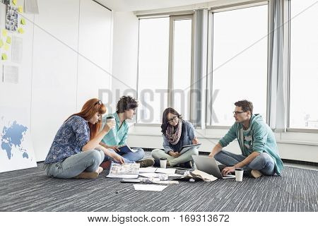 Businesspeople working on floor at creative work space