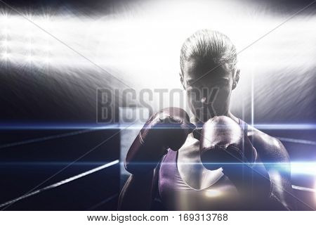 Portrait of woman fighter with gloves against black background
