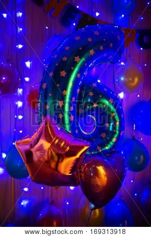 Number six birthday baloon in blue party light.