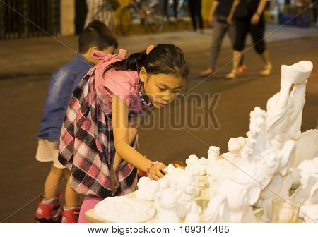 Hanoi, Vietnam - Nov 2, 2014: Child chooses clear plaster figurine before painting with color ink and brush on Ma May street, old quarter of Hanoi