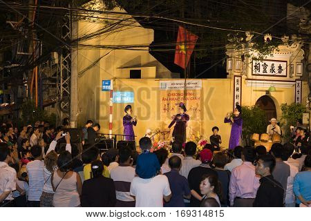Hanoi, Vietnam - Nov 2, 2014: Tourist watch a free show of ancient folk music and song on Ma May street, old quarter of Hanoi