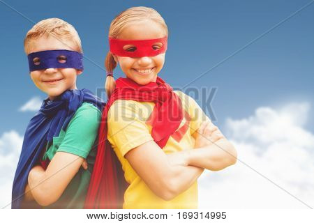 Happy brother and sister in cape and eye mask against blue sky