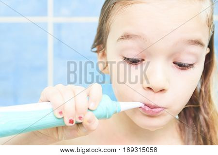 Close up of cute little girl in a bath and cleaning her teeth with electrical toothbrush against cool blue wall. Children hygiene.