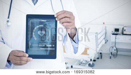 A doctor showing digital tablet against empty bed in the hospital room