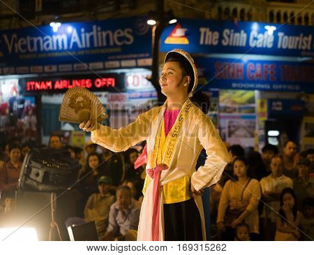 Hanoi, Vietnam - Nov 2, 2014: Vietnamese artists perform folk music and song on Ma May st, old town of Hanoi. The male artist plays the Holy Mother