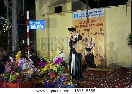 Hanoi, Vietnam - Nov 2, 2014: Vietnamese woman singer wears ancient clothes singing folk music and song on Ma May st, old town of Hanoi.