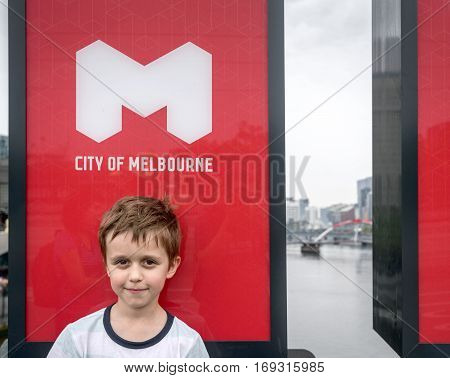 Melbourne Australia - December 27 2016: Cute smiliing boy standing under the City of Melbourne logo on the street