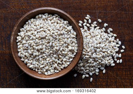 Dry Pearl Barley In Brown Wooden Bowl Isolated On Dark Wood From Above. Spilled Barley.