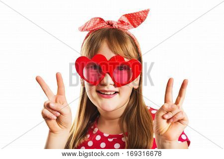 Funny portrait of a cute little girl wearing big heart shaped sun-glasses and polkadot headband, showing fingers peace sign, studio shot, isolated on white background