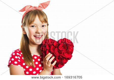 Studio shot of young little 9-10 year old girl, wearing red polka dot dress and headband, isolated on white background, pin up style, holding big decoration heart, Saint Valentine concept