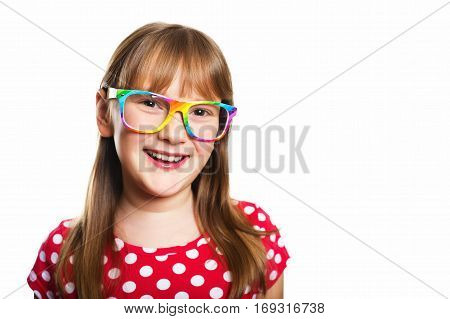 Studio portrait of adorable little 9-10 year old girl, wearing rainbow eyeglasses and red polka dot dress, standing against white background
