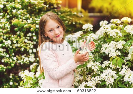 Outdoor portrait of 7-8 year old pretty little girl with spring flowers, wearing pink jacket