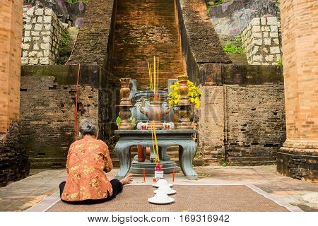 Brick cham towers in Nha Trang, Vietnam. Po Nagar. Ancient buddhism, indhuism towers. Praying woman. Colorful horizontal image