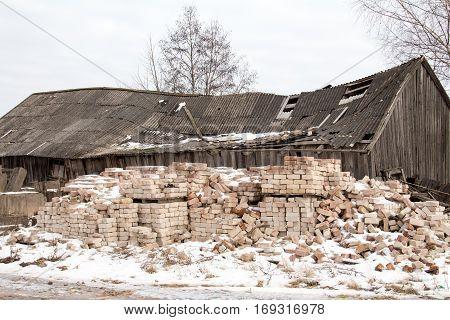 Pile of masonry bricks against abandoned and damaged building