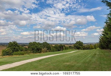 Essex countryside seen from a golf course. Shows a golf course with a beautiful blue and cloudy sky. Shot taken in late summer and shows the Essex Countryside in the background.