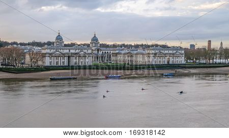 Royal Naval College at Greenwich, London. Shot in the early morning in winter at low tide of the Royal Naval College at Greenwich with the River Thames in the foreground and rowers.