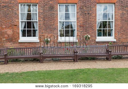 3 windows with 3 benches in front of them. Shot is set with a path and lawn in front of the benches and the windows of an elegant Georgian house.