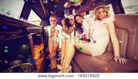 Portrait of female friends in limousine against flying colours