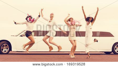 Happy friends jumping in front of a limousine on night out