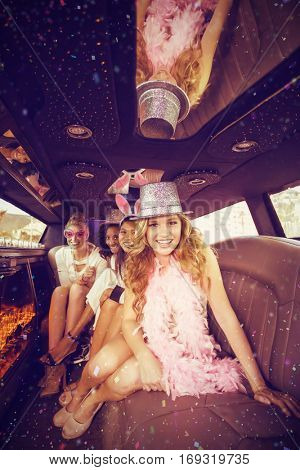 Female friends having fun in limousine against flying colours