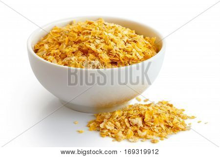 Dry Flaked Corn In White Ceramic Bowl Isolated On White. Spiled Flakes