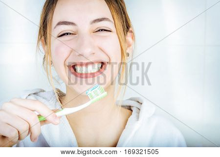 Happy young woman brushing teeth  on the bathroom.