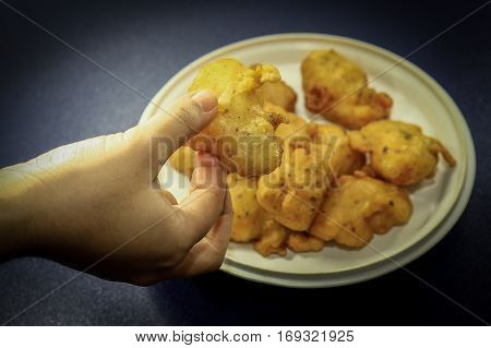Woman's hand holding Cucur Udang or Prawn Fritters,it's a common tea time cake among Malaysians.A popular snack in South East Asian countries.